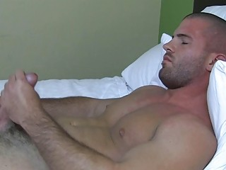Sexy muscled gay stud plays with his hard bazooka in bed