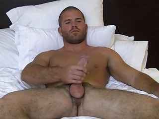 Muscled bald gay hunk wanks his big enduring cock on bed