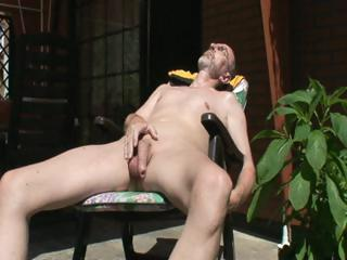 Old horny simian is outside sitting in a easy chair jerking off his cock
