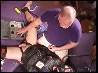 Dude in the air a leather straitjacket is fondled and teased by old guy