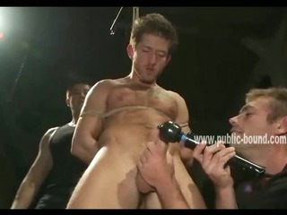 Gay sex slave is tied up and has his ass probed and dual on while having his cock sucked